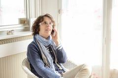 Une femme mûre avec un téléphone portable Photo stock