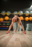 Une femme magnifique avec le corps parfait faisant l'étirage sur un fond de gymnase Concept aérobie, de forme physique et de body Image libre de droits