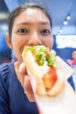 Une femme mangeant un hot-dog Photo stock