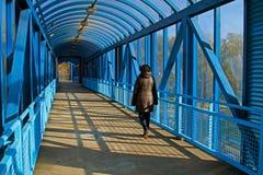 Une femme marche sur un pont piétonnier aérien Photo libre de droits