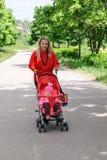 Une femme marche sur une allée verte avec un landau et un bébé Image stock