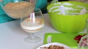 Une femme met dans les ingrédients en verre de couches pour faire le dessert Miettes et crème de biscuit Est tout près une fraise clips vidéos