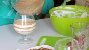 Une femme met dans les ingrédients en verre de couches pour faire le dessert Miettes et crème de biscuit Est tout près une fraise banque de vidéos