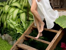 Une femme mince dans de longues courses blanches d'une robe en bas des ?tapes en bois ? la pelouse Les jambes se ferment  banque de vidéos