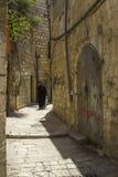 Une femme musulmane dans une petite rue étroite outre de par l'intermédiaire de Dolorosa dans J photo libre de droits