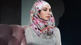 Une femme musulmane moderne avec les yeux peints dans le hijab regarde dans la distance clips vidéos