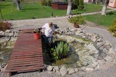 Une femme nettoie au printemps un étang artificiel photographie stock