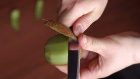 Une femme nettoie la peau de kiwi avec un couteau Plan rapproché banque de vidéos