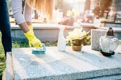 Une femme nettoie la tombe photographie stock