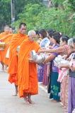 Une femme non identifiée donne la nourriture à un moine Photos libres de droits