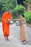 Une femme non identifiée donne la nourriture à un moine Images stock