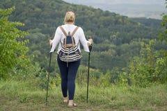 Une femme occup?e ? marcher nordique en parc Style de vie sain photographie stock libre de droits