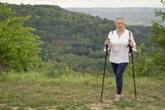 Une femme occup?e ? marcher nordique en parc Style de vie sain images stock