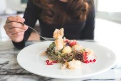 Une femme ont plaisir à manger de la salade de fruits mélangée avec les crevettes frites sur la table images stock