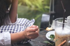 Une femme ont plaisir à manger du gâteau au fromage et du café en café images libres de droits