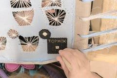 Une femme-ouvrière couturière brode avec un fil d'or un modèle sur le morceau de cuir image stock