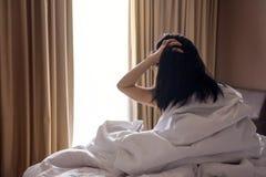 Une femme paresseuse avec les cheveux malpropres se reposant sur le lit blanc et regardant O Image libre de droits