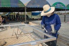 Une femme peint la barrière en métal de fil dans la couleur argentée Photos libres de droits