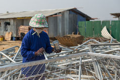 Une femme peint la barrière en métal de fil dans la couleur argentée Image stock