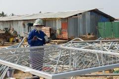 Une femme peint la barrière en métal de fil dans la couleur argentée Image libre de droits