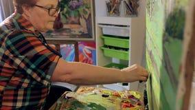 Une femme peint un paysage avec des peintures à l'huile avec une palette et un couteau banque de vidéos