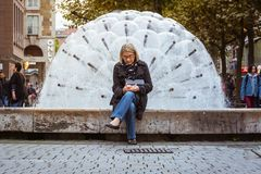 Une femme plus âgée à l'aide de la fontaine O de Stuttgart Koenigsstrasse de téléphone portable Image libre de droits