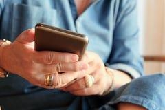 Une femme plus âgée à l'aide du téléphone intelligent Images stock