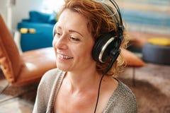 Une femme plus âgée écoutant la musique avec des écouteurs à la maison Photos libres de droits
