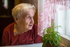 Une femme plus âgée avec désir ardent regarde la fenêtre triste photo libre de droits