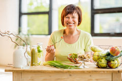 Une femme plus âgée avec la nourriture saine à l'intérieur photographie stock libre de droits