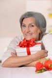Une femme plus âgée avec le cadeau Images stock