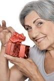 Une femme plus âgée avec un cadeau Photographie stock libre de droits