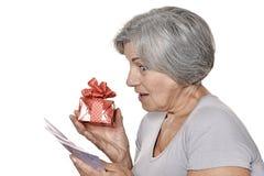 Une femme plus âgée avec un cadeau et un argent Image stock
