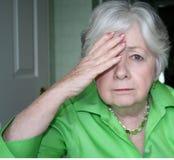 Une femme plus âgée avec une main à la tête Image libre de droits