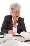 Une femme plus âgée d'affaires s'asseyant à la lecture de bureau dans un livre Concept Photos stock
