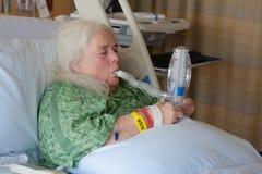Une femme plus âgée dans le lit d'hôpital utilisant le spiromètre encourageant photographie stock libre de droits