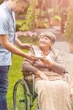 Une femme plus âgée dans un fauteuil roulant prenant une tasse de thé d'une infirmière photo libre de droits