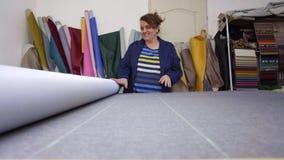Une femme plus âgée dans une usine de meubles prépare un matériel gris pour mesurer et couper clips vidéos