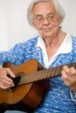 Une femme plus âgée jouant la guitare. Photo stock