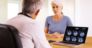 Une femme plus âgée parlant avec le docteur personnel au sujet de ses soucis de santé Images stock