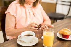 Une femme plus âgée prenant des pilules avant petit déjeuner Images libres de droits