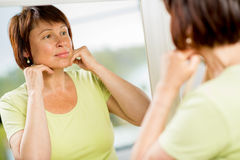 Une femme plus âgée regardant dans le miroir photo stock