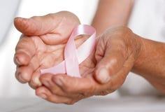 Une femme plus âgée remet tenir le ruban rose de conscience de cancer du sein photographie stock libre de droits
