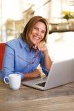 Une femme plus âgée s'asseyant à la table fonctionnant avec l'ordinateur portable photo stock