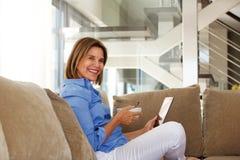 Une femme plus âgée s'asseyant sur le sofa avec la cuvette de petit déjeuner et de comprimé Image libre de droits