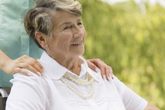 Une femme plus âgée s'asseyant sur un fauteuil roulant Images libres de droits