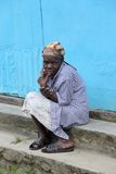 Une femme plus âgée s'assied sur des étapes du bâtiment de village Images libres de droits