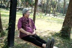 Une femme plus âgée se reposant dans le jardin détente femelle pluse âgé sur l'oscillation Images libres de droits