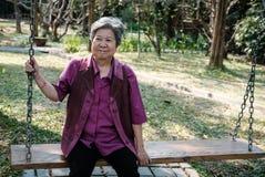 Une femme plus âgée se reposant dans le jardin détente femelle pluse âgé sur l'oscillation Image stock