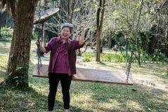 Une femme plus âgée se reposant dans le jardin détente femelle pluse âgé sur l'oscillation Photos stock